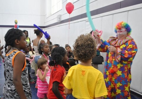 clown making balloon shapes for an audience of children