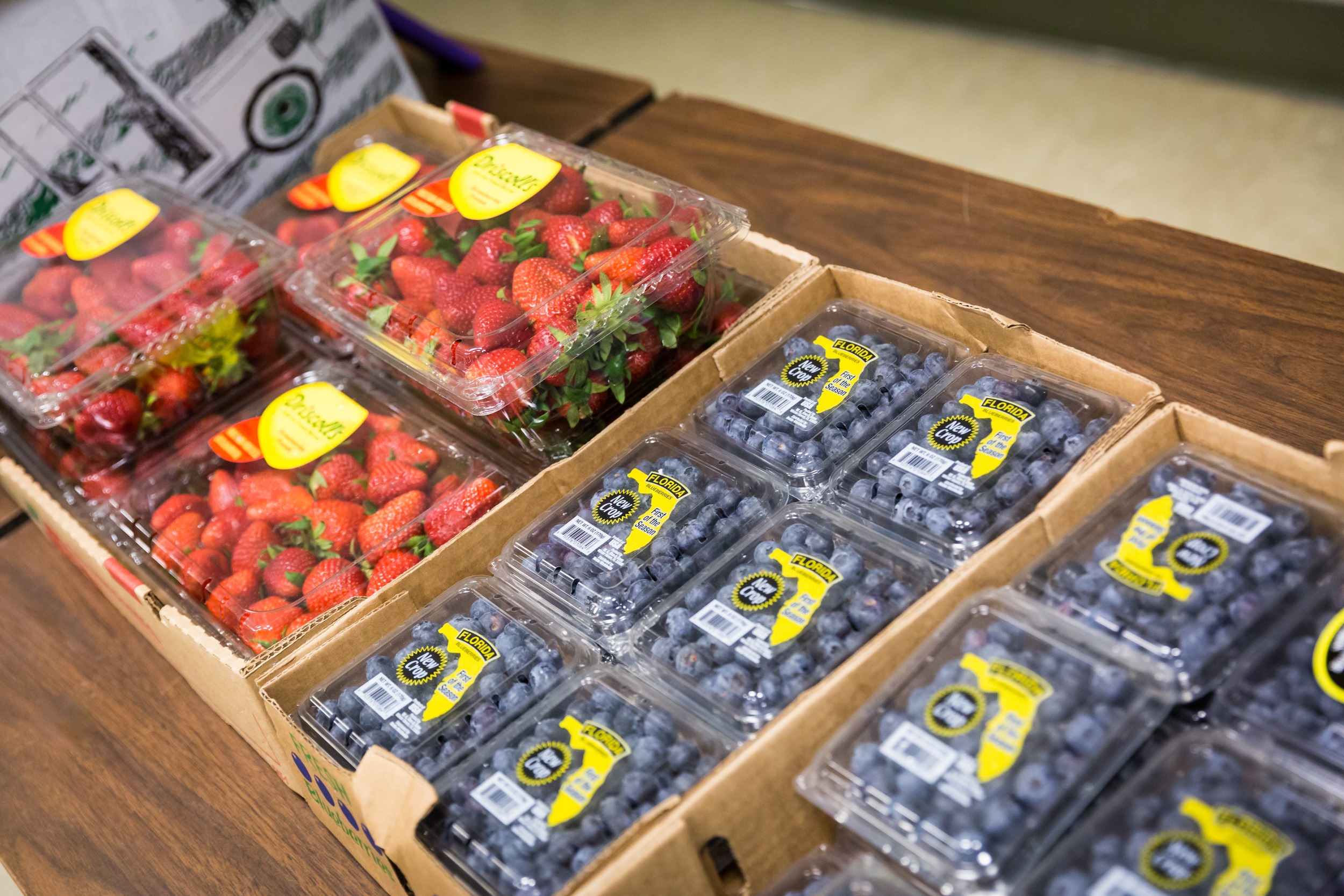 packages of strawberries and blueberries on a folding table for the food pantry