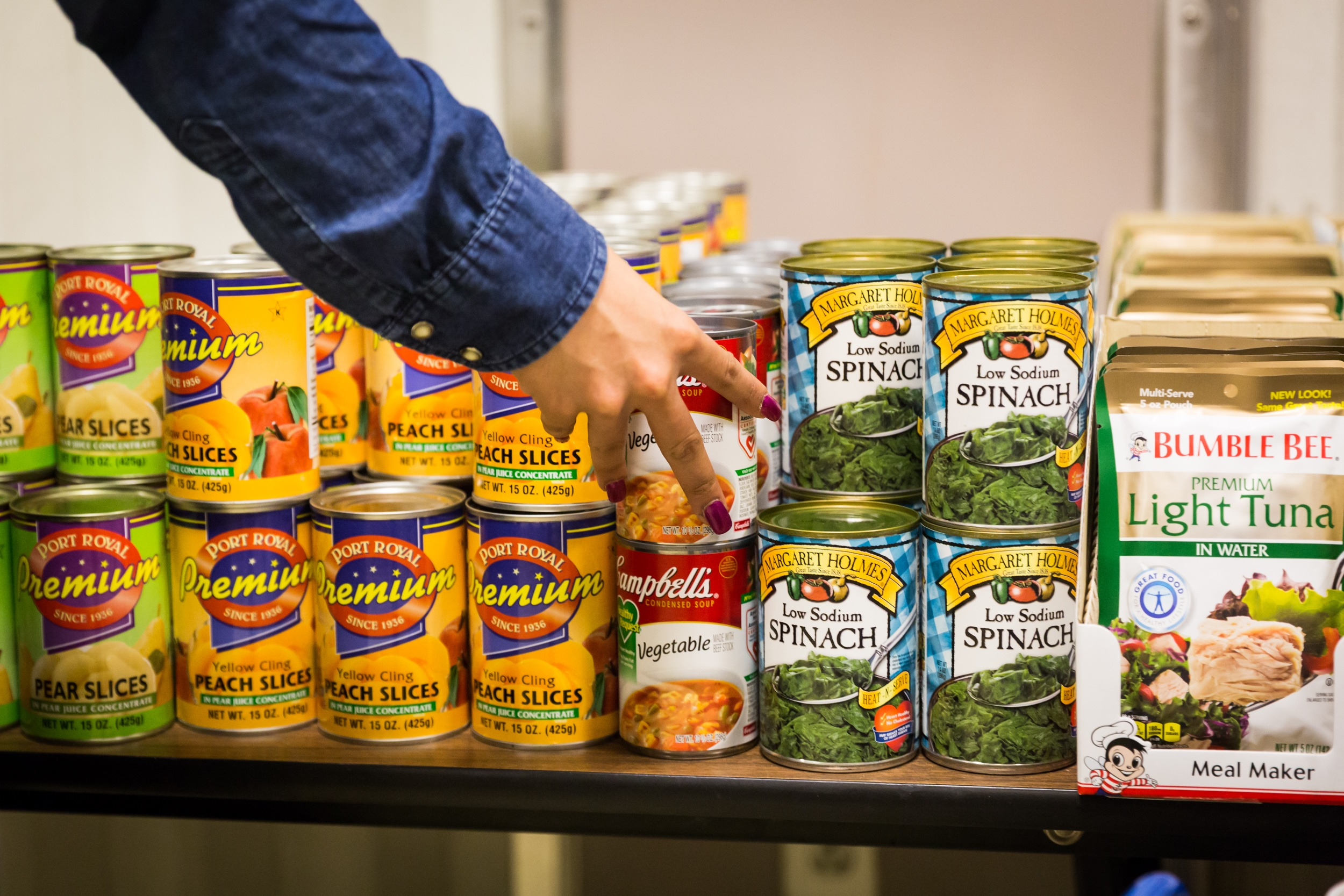cans of pears peaches vegetable soup spinach and packages of tuna on a folding table for the food pantry