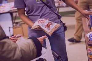 A food pantry volunteer handing out a package of beans